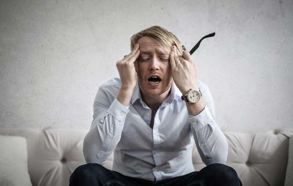 zmęczenie wypalenie zawodowe mężczyzna który trzyma się za głowę ma zamknięte oczy w ręku trzyma okulary